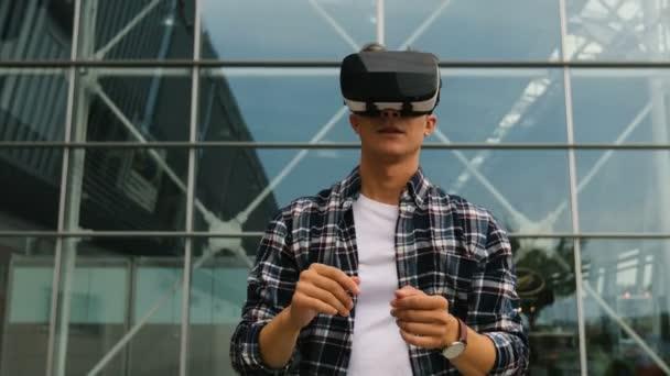 Porträt eines jungen kaukasischen Mannes mit Virtual-Reality-Brille, um das Video auf dem Hintergrund des modernen Flughafens anzusehen.