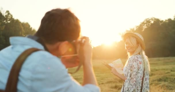 Rückansicht auf den männlichen Fotografen die Fotos auf der Kamera die blonde schöne Frau mit Hut und mit einer Karte in Händen. Sonnenuntergang auf dem Gebiet