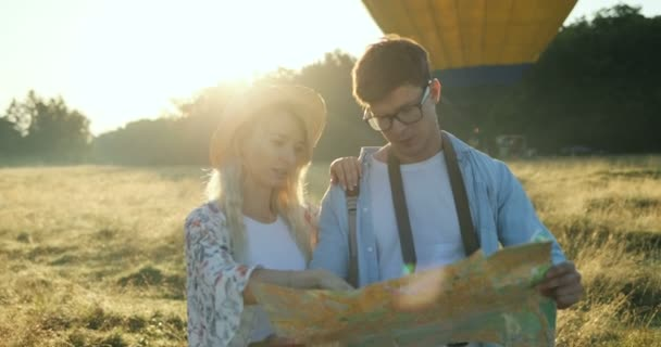 Caucasian young attractive man and woman standing in the field with a map on a sunset. Big balloon on the background.