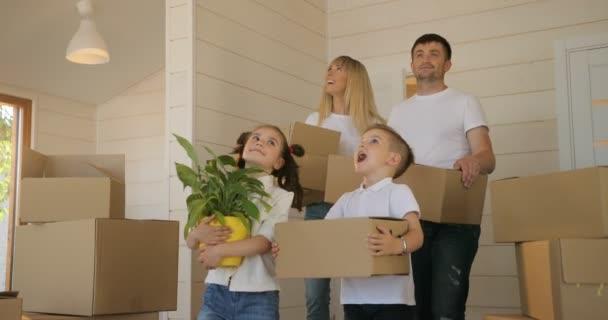 Familie zieht um in ein neues Zuhause. Junge, anspruchsvolle Familie trägt Pappkartons ins neue moderne Zuhause ins Wohnzimmer. Glückliche Familie mit Kartons im neuen Haus