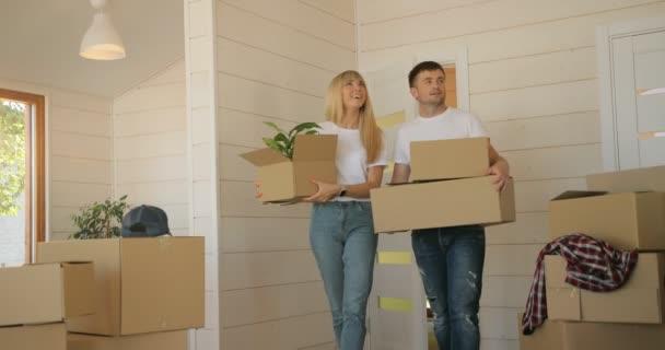Porträt eines Paares, das Pappkartons ins neue moderne Zuhause ins Wohnzimmer trägt. Paar zieht um, mietet Haus