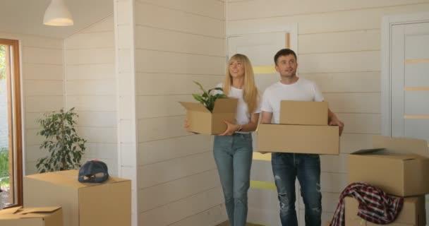 Porträt eines Paares, das Pappkartons ins neue moderne Zuhause ins Wohnzimmer trägt. Frau und Mann ziehen in neue Wohnung
