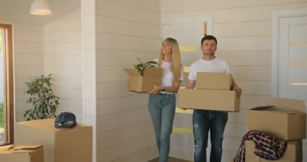 Porträt eines Paares, das Pappkartons ins neue moderne Zuhause ins Wohnzimmer trägt. Paar zieht in ein neues Zuhause.