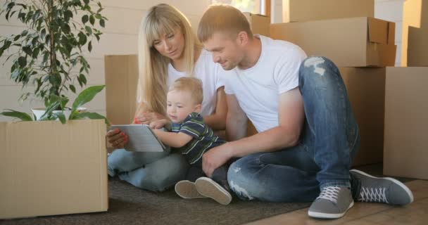Husband and wife and their son moving in new home. Mortgage, people, housing and real estate concept - happy family with tablet pc computer moving to new house