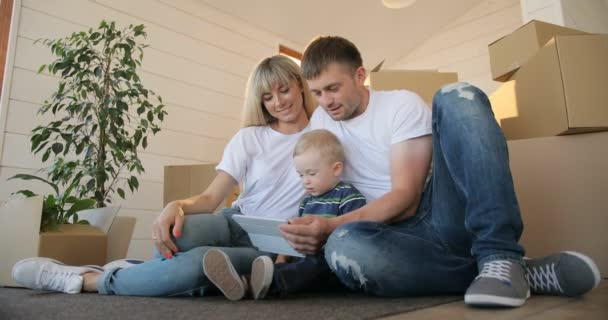 Husband and wife and their son moving in new home. Mortgage, people, housing and real estate concept. Happy family portrait with tablet pc computer moving to new house