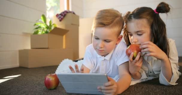 Happy sourozenci dítě hraje s pc tablet dohromady. Bratr a sestra spolu hrát v hrách na tabletu v novém domě. Krabice zázemí