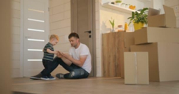 Portrét otce a syna s boxy zázemí, hrát spolu v novém bytě. Hypotéky, přesouvání a realit koncept.