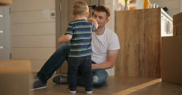 Portrait of father and little son playing together at new apartment. Mortgage, moving and real estate concept.