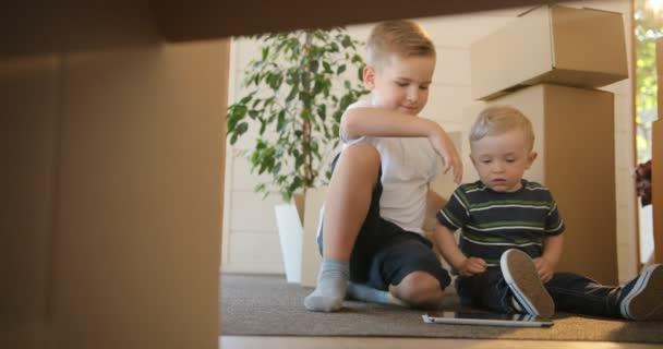 Porträt zweier kleiner Jungen, die in ihrem neuen Haus Spaß haben - beim Spielen oder Lesen vom Tablet. Brüder interessieren sich für die Nutzung und das Spielen digitaler Tablets. Bildung, Hypothek, Wohnungs- und Immobilienkonzept.