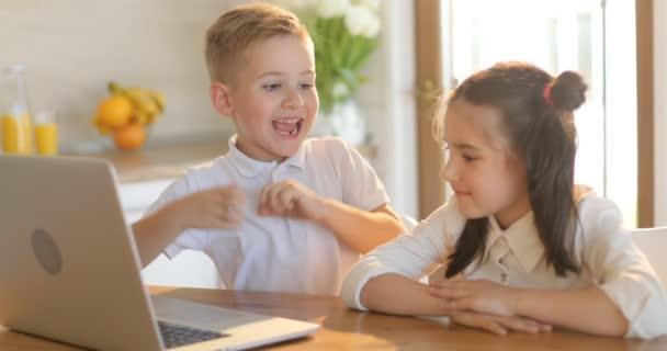 Děti s přenosným počítačem. malý chlapec a dívka sledovat pořady online. Šťastné děti podívat na kreslený v kuchyni, baví