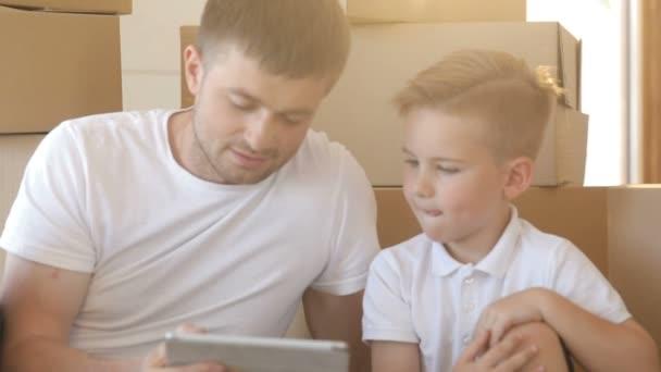 Portrét otce a syna s boxy zázemí, hrál v tabletovém počítači v novém bytě. Hypotéky, přesouvání a realit koncept.
