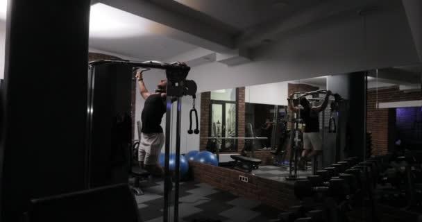 Atraktivní mladá dospělá žena dělá pull ups v tělocvičně. Sportovní mužské školení sportovní a fitness koncept. Cvičení cvičení