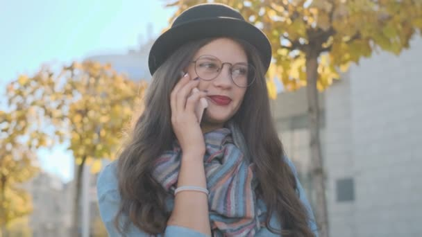 Portrait of beautiful girl wearing hat talking on smartphone outdoor. Conversation on mobile phone.