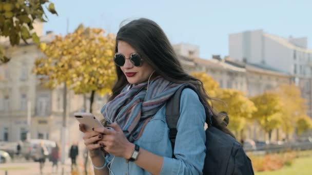 Close up portrait of texting woman on a smartphone device. Beautiful young woman using modern smart phone typing text message and listening to music on cellphone outside