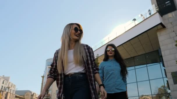 Happy young girlfriends embracing. Two happy girls friends giving piggyback, laughing and walking on sunny city background.