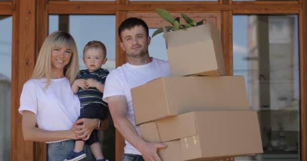 Šťastný manželský pár s malým synem v novém domě. Nákup nemovitosti, hypotéky, pohybující se koncept. Rodina s karton krabice v novém domě v den stěhování.