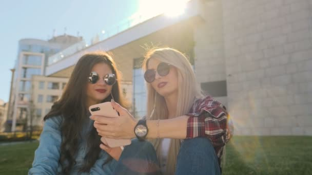 Two happy girlfriends listen to music on headphones while hanging out in park.