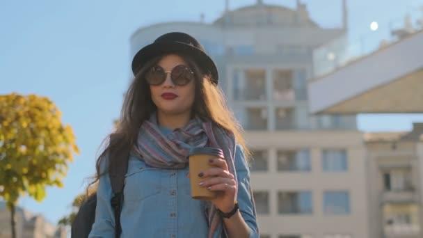 Módní portrét mladé stylové hipster ženy chůzi na ulici, na sobě roztomilé módní oblečení a tmavý klobouk, pití horké latte