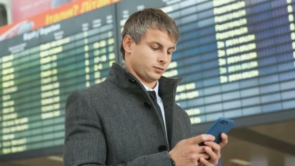 Portrét vážný podnikatel v oblek a kabát pomocí chytrého telefonu pro kontrolu svůj let na pozadí příchozí elektronické tabulky