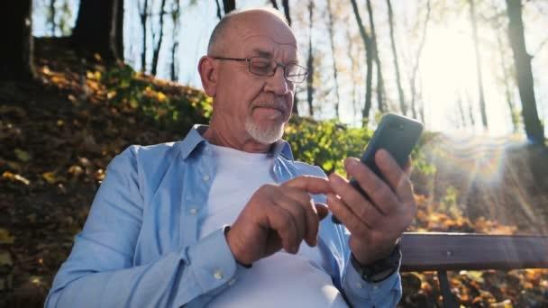 Starší muž pomocí mobilních telefonů, hospodářství chytrý telefon, SMS, procházení Internetu a pomocí app. záběr Portrét muže s plnovousem a nosíš brýle, sedí na lavičce v parku a používá zařízení