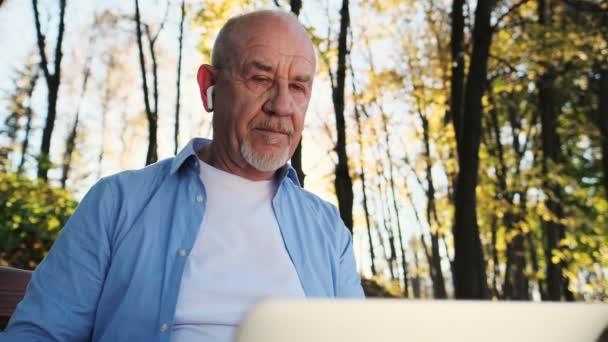 Otec sedí na lavičce v parku a hir počítač používá. Zblízka portrét starší muž s bradkou pomocí přenosného počítače venkovní
