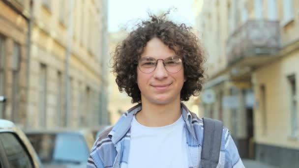 Zavřete portrét mladý usmívající se muž s kudrnatými vlasy vlající ve větru a brýle, při pohledu na fotoaparát. V Evropě. Zpomalený pohyb. Student, urbanistický koncept.
