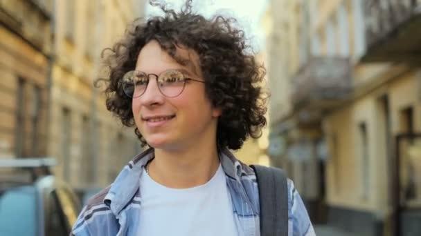 Portré, fiatal, mosolygó ember, göndör hajú, fúj a szél és a szemüveg, látszó-on fényképezőgép, sétáló utca a régi város központja Európában közelről. Lassú mozgás. Diák, koncepció.