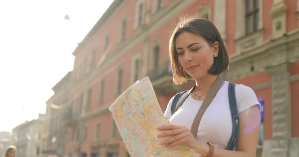 A girl is opening a map and looking for some place