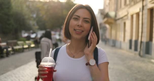 Egy lány, egy ital mellett válaszoló őt telefonon, és nevetve