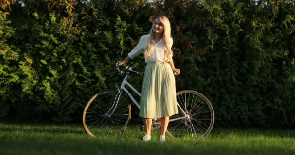 Beautiful smiling young woman portrait with bike. Fashion pretty girl in drees with retro vintage bicycle standing over green natural background and looking at camera