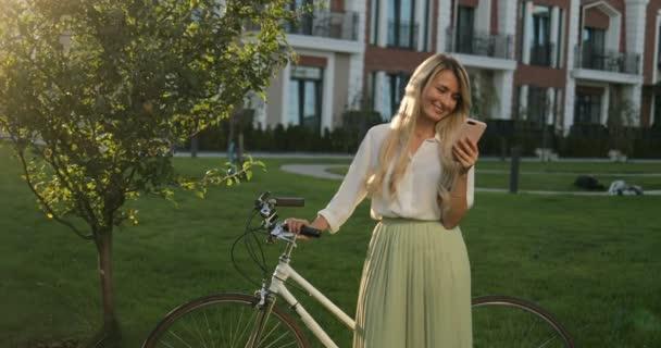 Mladá krásná žena s chytrý telefon pomocí aplikace a textových zpráv. Happy krásná dívka s bike venkovní, při pohledu na fotoaparát.