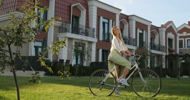 Fiatal gyönyörű csípő nő zöld ruhában, nyári trend stílusú, strand, lovaglás kerékpár, utazás, mosolygó, boldog, pozitív, kacér. Szép, boldog fiatal lány vintage kerékpár, mosolyog kamera