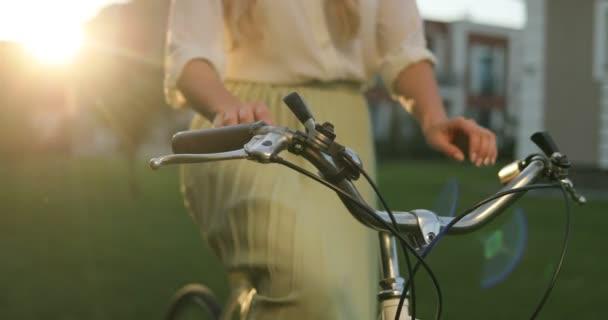 Koncept zdravého životního stylu. Dívka na koni na kole v parku. Dvě ruce na vintage bike řídítka. Detailní záběr ženy, jízda na kole