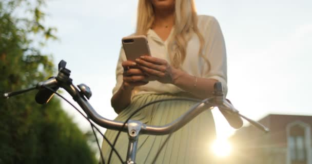 Healthy lifestyle concept. Girl riding a bicycle in the park using smarphone, texting at phone,and using app. Close up of woman riding on bike
