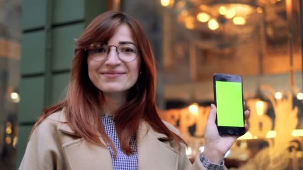 Attraktive junge Frau zeigt Smartphone mit Chroma-Key, grünen Bildschirm. Schöne Frau mit Smartphone-Technologie app zu Fuß durch die Straßen der Stadt Leben glücklich Urbanität