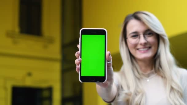 Attraktive junge Frau zeigt Smartphone mit Chroma-Key, grünen Bildschirm. Schöne Frau mit Smartphone-Technologie app zu Fuß durch die Straßen der Stadt.