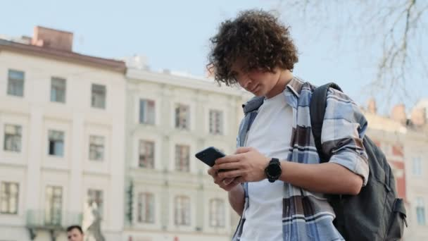 Handsome young man, tourist or student, millennial in hipster outfit, using his smartphone scrolls through social media feed on device, checking map or reading news on app, looking around