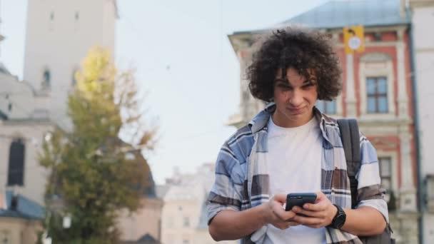 Portrét atraktivní mladý muž, turistické nebo student, generace z nebo milénia v hipster oblečení, roztržitý sociální média nebo herní aplikace, pohledy do novinky krmiva na smartphone