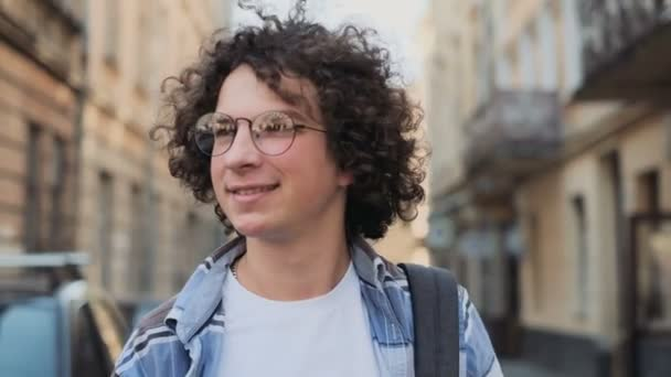 Smiling and laughing handsome young man. Happy attractive caucasian hipster walking outside and looking around. Curly man, tourist or student, millennial in hipster outfit, outdoor, looking at camera