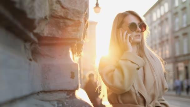 Portrét krásné módní kavkazské ženy mluví o smartphone, užívat si života městské města. Dívka na mobil, na sobě kabát, venku.