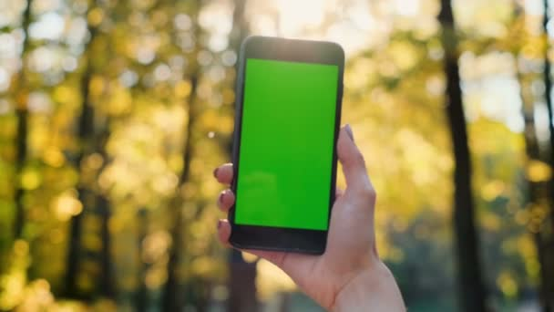Mädchen zeigt Telefon grünen Bildschirm im Freien, städtischen Umgebungen. Frau hält Smartphone mit Chroma-Schlüssel in der Hand. Schuss von der Rückseite. Außenbereich.