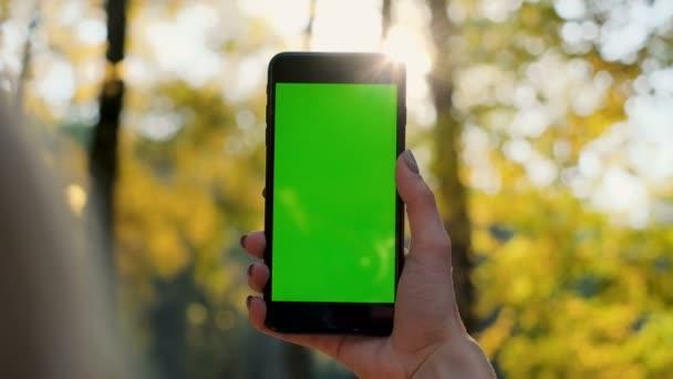Lány mutatja a telefon zöld képernyő szabadban, városi környezetvédelmi. Nő kezében smartphone chroma-kulcs. Közelről nő kezében tartja, és a függőleges zöld képernyő segítségével mobil okos telefon.