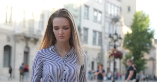 Pretty young blonde woman walking on the street during a suuny day using her mobile phone and texting.