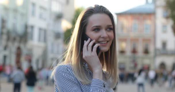 Young attractive blonde in a shirt is talking on the phone on the street and smiling, close-up view