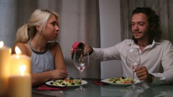 A handsome men is pouring wine for his wife on a dinner