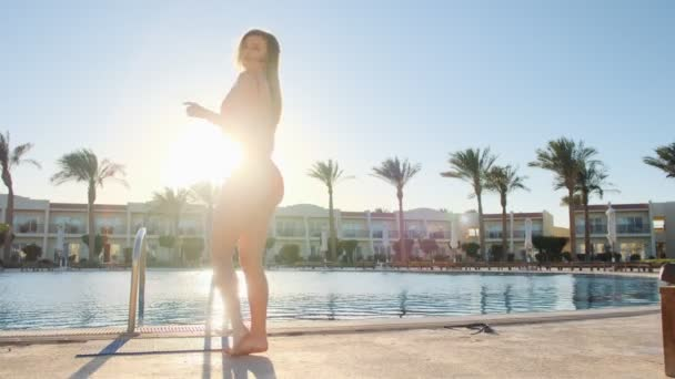 Beautiful attractive woman in red swimsuit dancing near clear blue swimming pool on hot sunny day. Crazy bikini girl having good time on summer holiday, at luxury spa resort