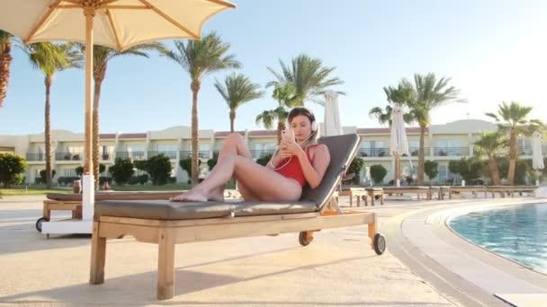 Atraktivní mladá žena v červené bikiny poslech hudby ze svého smartphonu v bílých sluchátek, zatímco leží na lehátku v bazénu straně hotelu. Dívka, opalování a relaxaci na resort.
