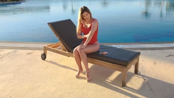Atraktivní dívka v červené plavky použití sluneční krém na opálenou kůži chránit pokožku a zabránit stárnutí od slunce. Opalování na Exotický resort poblíž straně bazénu