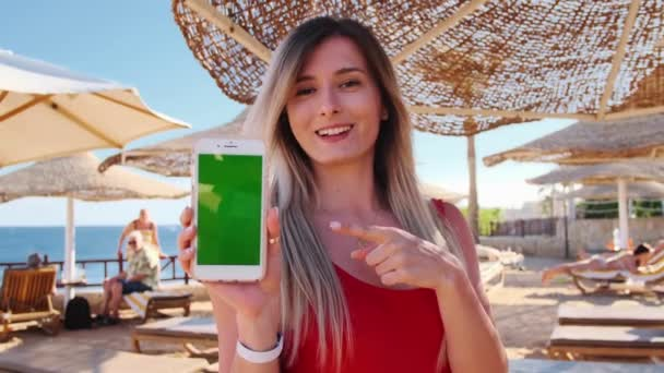 Girl on vacation show the green screen smartphone outdoor. Close up woman hand holding and using mobile smart phone with vertical chroma key. Sexy woman in red body using mobile phone at luxury hotel.