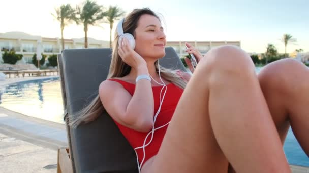 Smiling young woman in red bikini and white headphones dancing and listening music from her smartphone, while lying on deck chair in hotel pool side area. Girl sunbathing and relaxing at resort.